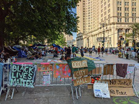"""尽管纽约市警被削10亿美元经费,""""占领市政厅""""人士仍不离场。图为运动分子2日在市政厅旁边的公园里做持久驻扎。"""
