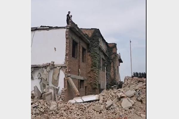 南省洛阳市洛龙区刘富村被强拆,村民站在房顶对抗拆迁人员。(受访人提供)