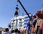 塔利班在城市广场用吊车示众罪犯尸体