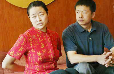 周雪菲和丈夫山姆-呂(朝暉)一起,示範當她因修煉法輪功而被關在勞教所時,如何長時間被強制把雙臂置於背後。