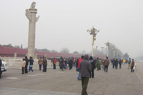 带有头饰的少数民族被疑为献花圈被警察按在灯杆下﹐验明身份后释放(大纪元图片﹐1月28日摄)