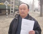 手拿訴狀的王偉在北京南站(大紀元)