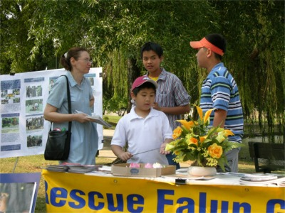亨城时报记者(左)在采访汽车之旅成员(大纪元)。