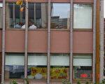 """中加人权对话会议正在二楼进行,中方代表不断的囬头观望窗外举行抗议活动的法轮功,窗上影岀的是""""法轮大法好""""横幅。(大纪元)"""