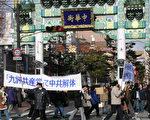 """举著日语标语""""'九评中国共产党'使中共解体""""横幅的游行队伍经过横滨中华街。(大纪元)"""