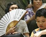 内地媒体报导指,深圳有人安排孕妇到香港产子,以取得香港居留权及永久居民身份。图为本月17日,数百名争取内地子女居港权的香港市民游行到中区政府总部抗议,要求尽快批准他们的子女到香港团聚。一名老婆婆带着孙儿参加示威活动。(MIKE CLARKE/AFP/Getty Images)