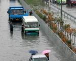 2006年7月31日北京的街道被雨水淹没﹐许多汽车熄火﹐有的人只好推著车走。(Photo by China Photos/Getty Images)