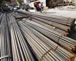 2006年9月13日。一北京三轮车夫经过一堆放在建筑工地旁的钢条。北京政府正在经受生产过度的危机﹐采取宏观调控来减缓过热的经济。(PETER PARKS/AFP/Getty Images)