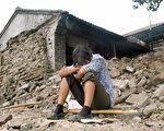 小女孩趴在倒塌的屋邊(GOH CHAI HIN/ Gettyimages)