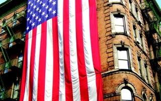 一幅高60尺寬30尺重80磅的巨型美國旗在曼哈頓勿街116號大廈掛起。(攝影 文忠/大紀元)