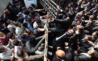 """2007 年11月29 日,巴基斯坦总统穆夏拉夫(Pervez Musharraf)宣誓就职时,律师走出拉合尔主要法院并高喊""""穆夏拉夫滚蛋""""的口号,遭警方以警棍殴打驱赶。(Arif Ali/AFP/Getty Images)"""