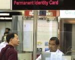 圖為一名香港市民由大陸返港,正在香港人境處櫃位接受職員審核身份。(AFP)