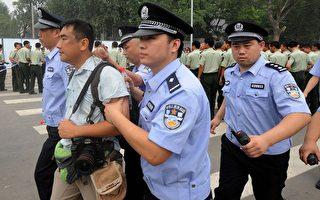 7月25日,香港多家媒體採訪北京開售奧運門票的混亂情況時,多名記者被公安粗暴對待,圖中的《南華早報》攝影記者被數名公安押帶。據指,他在公安局被迫跪下。報社後來向當局致歉,他亦才獲釋。(AFP)