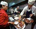 厨房里挤,人多、东西多、油烟多、活多、叫喊声多,什么都多,就是休息少。(LIU JIN/AFP/Getty Images)
