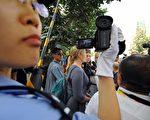 中国警察正在拍摄接受记者采访的外国示威者(22日/GOH CHAI HIN/AFP/Getty Images)