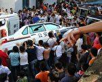 图:贵州628瓮安事件现场。民众掀翻警车。(新唐人图片)