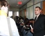 3月31日,紐約市食物銀行宣布為居民免費報稅和申請「所得稅抵扣」退款,圖為食物銀行工作人員向記者們介紹其服務的情況。圖中坐著排隊的是前來尋求幫助的居民。(攝影:鐘濤/大紀元)