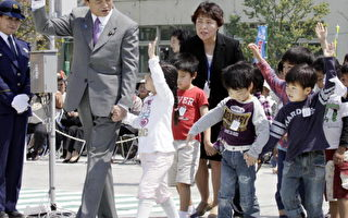 當地時間13日,日本首相麻生太郎出現在交通安全宣傳周活動中,帶領著一群小學生走斑馬線穿越馬路。(YOSHIKAZU TSUNO/AFP/Getty Images)