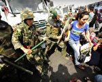 7月6日,新疆乌鲁木齐街头,手持棍棒的警察推挤维族妇女。(AFP PHOTO)
