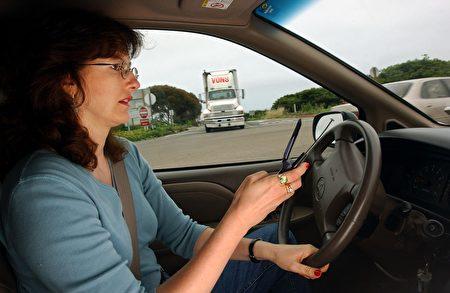 最新研究發現,開車發送簡訊的危險性遠高於撥打手機,幾乎等同於酒後駕車。 圖為加州一名婦女於駕駛中正在使用手機。(David McNew/Getty Images)