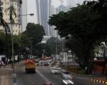 由於馬來西亞婆羅洲和鄰國森林大火延燒導致空氣品質下降到不健康水平,造成能見度低。圖示8月5日煙霧迷漫的吉隆坡市中心駕駛者在白天使用他們的車燈行駛。 (SAEED KHAN/AFP/Getty Images)