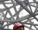 """前北京奥申委执行主席袁伟民近日推出的《袁伟民与体坛风云》一书爆料,罗格是通过北京申奥委员会的""""院外游说工作"""",才得以于2001年在莫斯科当选国际奥委会主席的,是罗格与中国的政治局达成的一个秘密交易。图为2006年10月24日,罗格在北京奥运会的主体育场施工现场(鸟巢)。(Takanori Sekine-Pool/Getty Images)"""