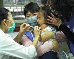 医护人员于秀朗国小为学童施打新流感疫苗,由爱心妈妈在旁协助、安抚学童情绪。(摄影:江禹婵/大纪元)