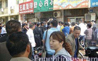2010年5月10日9點,河南平頂山棉紡廠一百多名女職工阻路維權,她們高喊口號,要求當地政府解決生計問題。圖為當地警察開始抓捕工人,家屬及圍觀群眾上前阻擋。(大紀元)