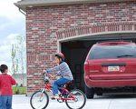 人們可能不能相信私家車道對孩童來說存在著很大的安全隱患。倒車或孩童從車道忽然衝到馬路上,是車道意外發生的兩大部分。圖為兩小童在車道上停泊的汽車附近玩耍。(攝影:岳怡/大紀元)