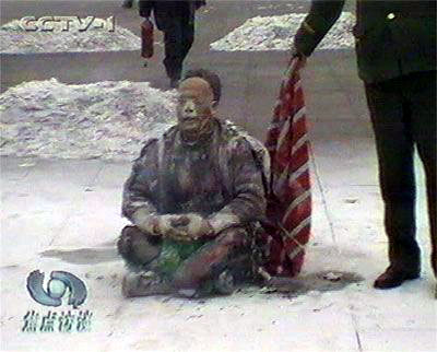 王進東穩穩的坐著,大聲喊清楚,表明身份後才能蓋上毯子。王進東兩腿之間盛汽油的綠色塑料瓶在「大火」之後竟然完好無損(視頻截圖)