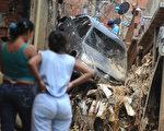 颶風「馬修」(Matthew)今天橫掃中美洲,風雨造成加勒比海內灣水災和土石流,至少14人因此喪命。圖為9月25日在委內瑞拉加拉加斯,居民無奈地注視著暴雨造成的災難。(MIGUEL GUTIERREZ/AFP/Getty Images)