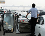 11月25日,《人民日報》發表文章,稱許多北京市民抱怨說「首都變『首堵』,房子又貴得出奇,這北京真是沒法住了。」圖為今年10月2日北京市交通阻塞情景。(STR/AFP/Getty Images)
