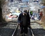2011年4月12日,岩手縣大槌市,一名老人走在順著鐵軌走回自己的家(AFP PHOTO / JIJI PRESS)