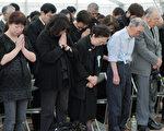 2011年6月18日,日本宮城縣石卷市舉行的震後百日紀念儀式上,地震和海嘯遇難者的親屬為逝者禱告。(AFP PHOTO / JIJI PRESS)
