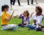 二零一一年七月二十一日是比利時國慶節,首都布魯塞爾的大街小巷上人頭攢動,熱鬧非凡。比利時的皇家公園作為主辦節日慶祝的地點被裝扮得喜氣洋洋。介紹法輪大法的展台在這喜慶的日子裡格外受到歡迎。圖為大學教授維羅尼卡和她的女兒在認真地跟著法輪功學員學習功法。