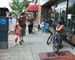 雨停后,人们外出就餐,逛商店,去教堂,或坐在屋外喝茶,街边呈现一派轻松景象。(摄影:李新/大纪元)