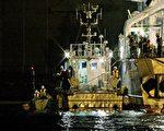 9月13日,9名朝鮮難民搭乘一條木舢舨安全漂浮到日本。圖為日本海上保安廳人員檢查停泊在石川縣金澤市港口的木舢舨(圖左)(STR/AFP/Getty Images)