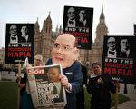 小默多克在議會接受質詢時,場外的抗議人士帶著模仿他的面具,手裡拿著一份諷刺他的報紙,把新聞國際旗下的《太陽報》(the Sun)故意寫成the Son,諷刺默多克父子,後面的抗議者手裡的牌子上面寫著「終止默多克黑手黨」。(Peter Macdiarmid/Getty Images)