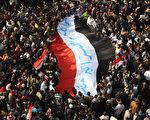 11月25日,抗议者扛着埃及国旗,在首都开罗的塔利尔广场(Tahrir Square)举行大集会,抗议军政府。(Peter Macdiarmid/Getty Images)