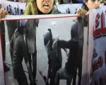 """2011年12月20日,抗议的妇女高举被殴打女性的照片,高喊""""尊严是她们的底线"""",不容轻侮的口号。(AFP PHOTO/KHALED DESOUKI)"""