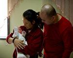 一些中國人和美籍華人希望龍年迎來「龍子」,紛紛開始接受生育治療,增加生龍寶寶的機率。圖為26日北京醫院一對夫妻喜迎龍女。(Ed Jones / AFP)