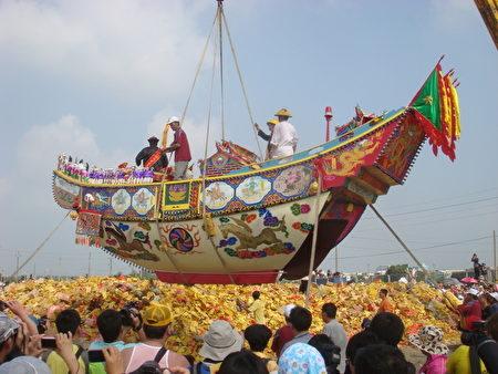 吊车将王船高高吊起,安放在堆积如山的金纸上,即将展开整个王醮的最高潮--烧王船。(陈素琴/大纪元)