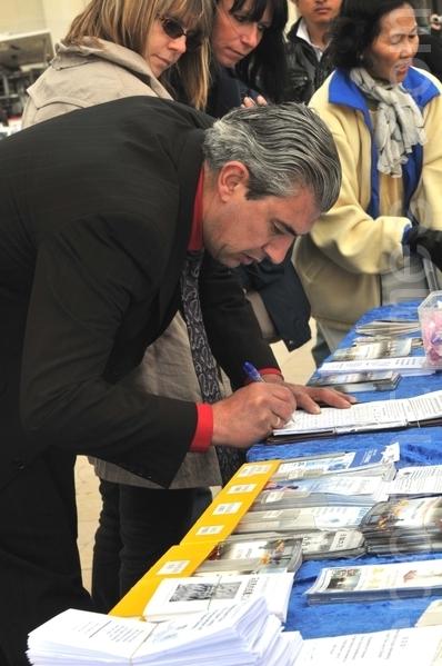行人在聽完真相後,簽名支持法輪功學員反迫害(攝影:本杰明/大紀元)