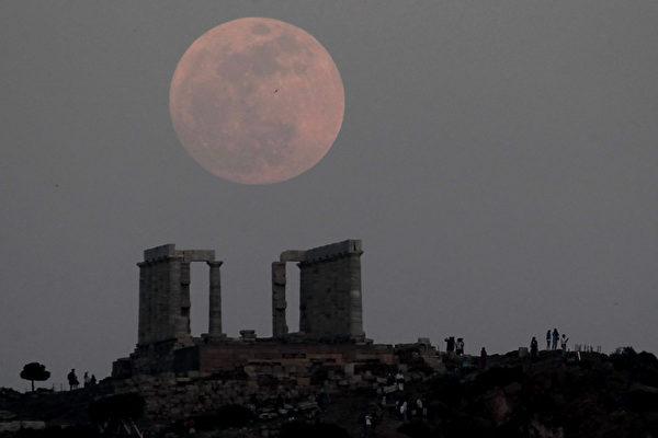 超級月亮照耀下的希臘雅典的一座古老的廟宇。(ARIS MESSINIS / AFP)