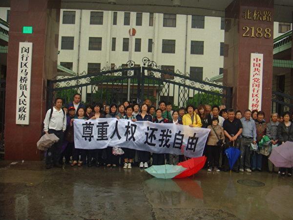 访民们冒雨在马桥镇政府门口打出横幅(访民提供)