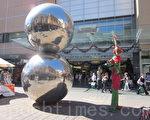 街头艺人在蓝道街的双球雕塑旁表演。(摄影:戴宁 / 大纪元)