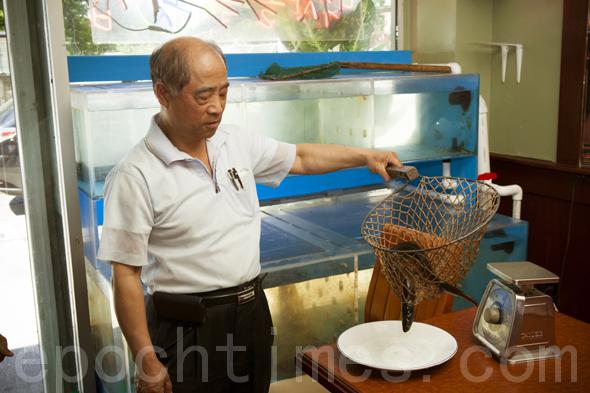 老闆安吾吉先生正在為顧客選新鮮活魚。(攝影:愛德華/大紀元)