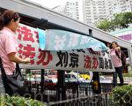 """穿着粉红色制服的""""香港青年关爱协会""""中共帮凶,用带来的横幅掩盖法轮功学员的横幅,故意挑衅香港法轮功学员。(摄影:潘在殊/大纪元)"""