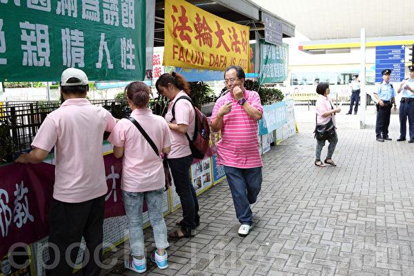 """穿着粉红色制服的""""香港青年关爱协会""""中共帮凶在绑横幅,负责人林国安在旁指挥。(摄影:潘在殊/大纪元)"""
