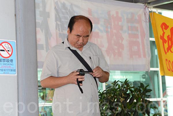 这名中共帮凶用小型摄影机对准学员拍摄。(摄影:邝天明/大纪元)